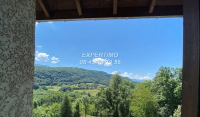 Vente de maison de village avec cuisine ouverte sur séjour donnant sur une terrasse avec vue sur les montagnes à St Etienne de Crossey